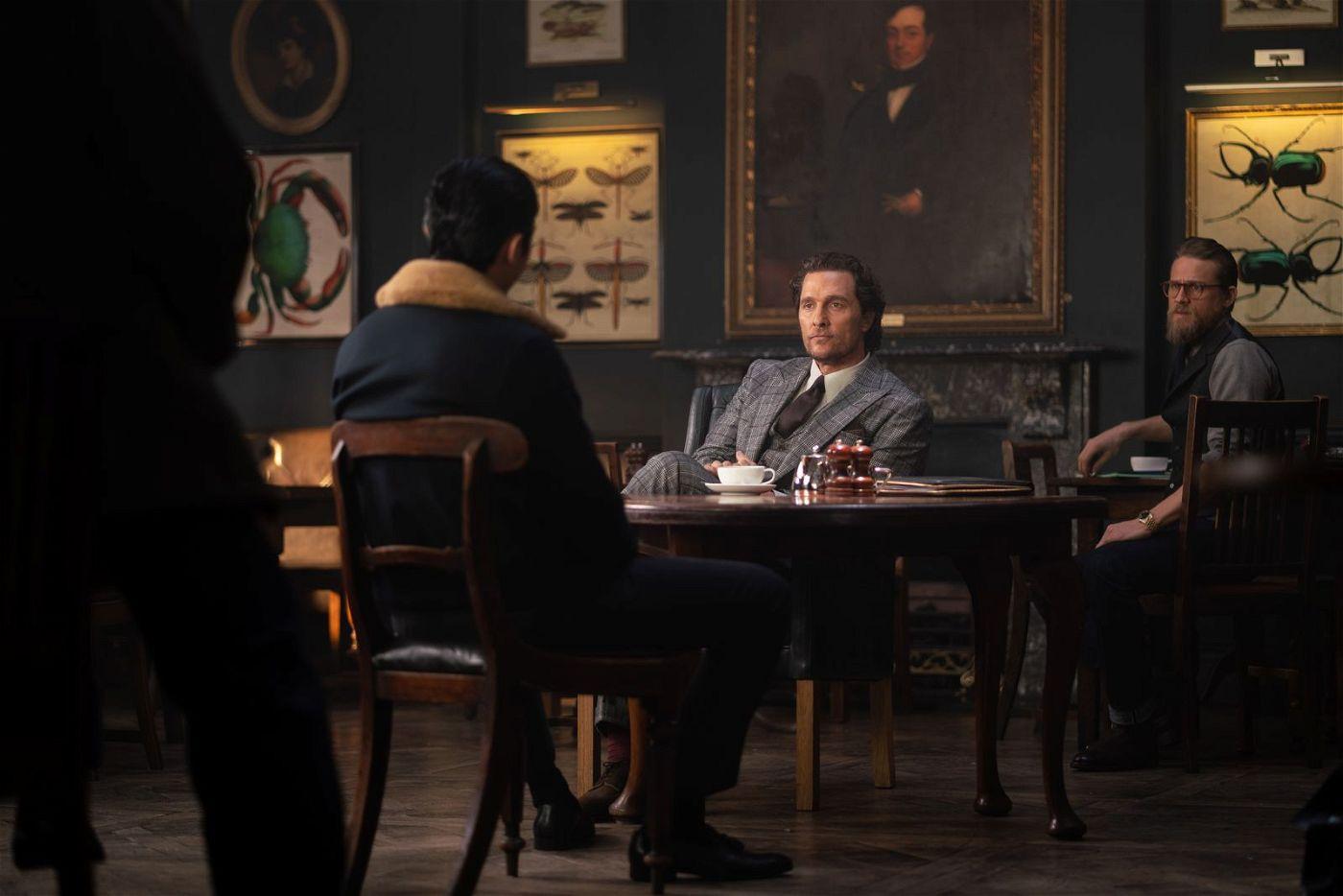 """Der Kleingangster """"Dry Eye"""" (Henry Golding, links) macht  Mickey Pearson (Matthew McConaughey, Mitte) und seiner rechten Hand Ray (Charlie Hunnam) ein Angebot."""
