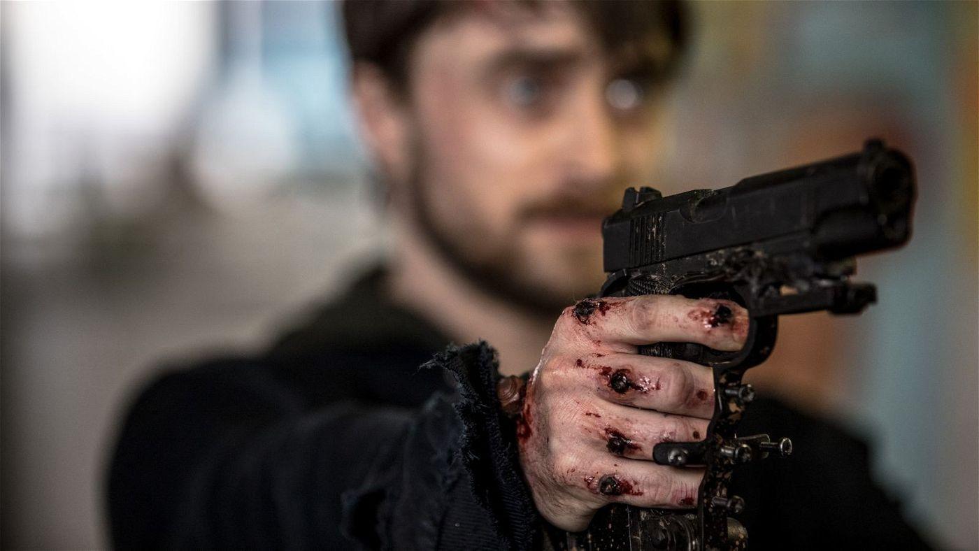 Durch die angeschraubten Pistolen kann Miles (Daniel Radcliffe) seine Hände nicht benutzen.