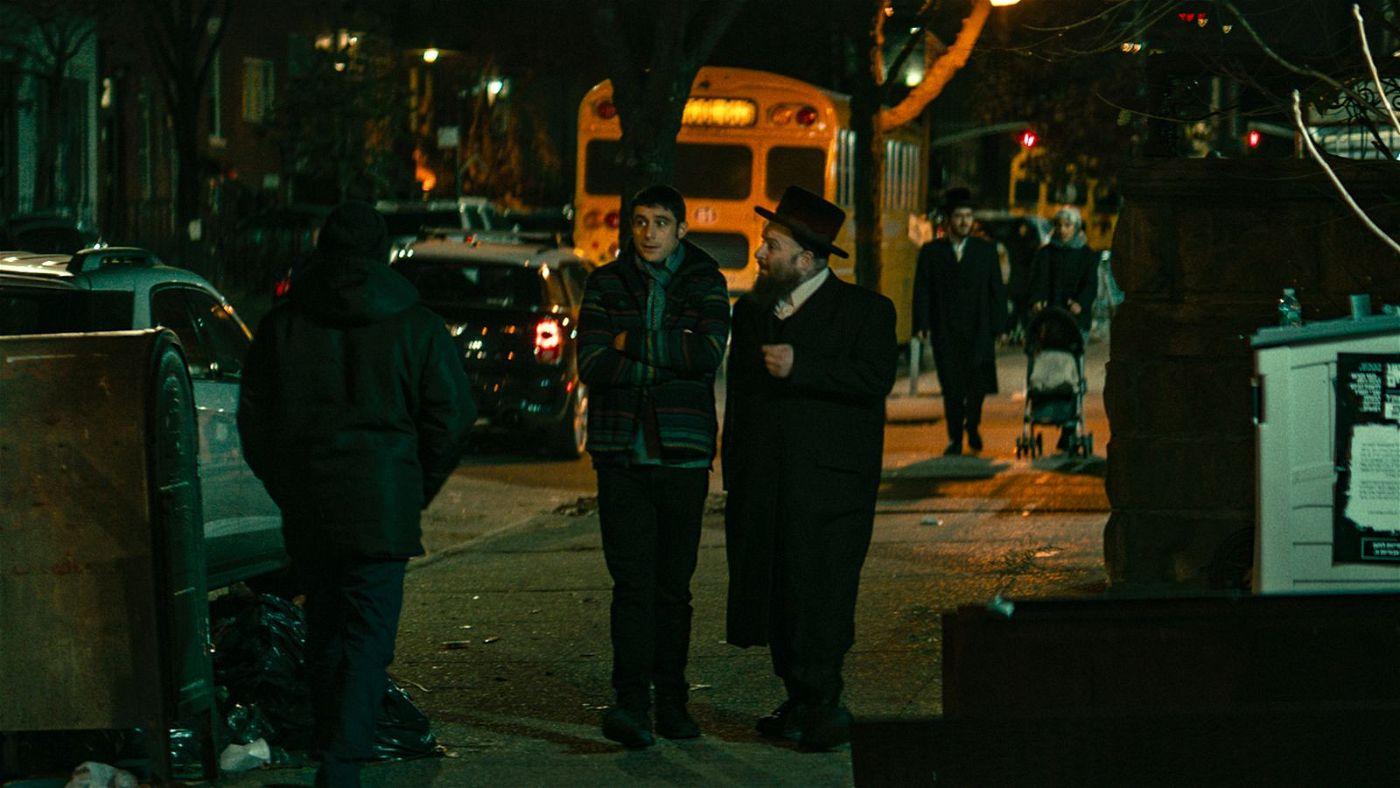 Der Rabbi (Menashe Lustig, rechts) aus seiner früheren Gemeinde überredet Yakov (Dave Davis, Mitte), die Totenwache zu übernehmen.