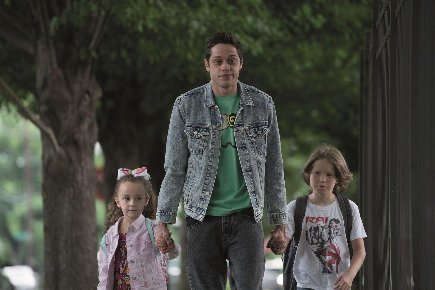 Weil seine Mutter den Feuerwehrmann Ray datet, muss Scott (Pete Davidson, Mitte) fortan dessen Kinder Kelly (Alexis Rae Forlenza) und Harold (Luke David Blumm) zur Schule bringen.